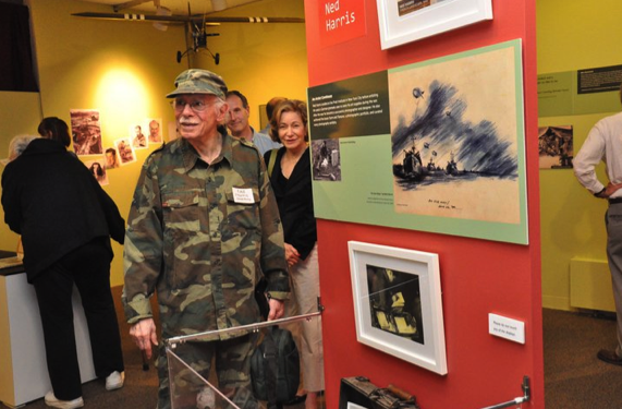 Ghost Army Veteran, Ned Harris near an display of his art work.