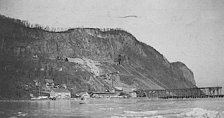 This large quarry was at the end of North Broadway in Upper Nyack, NY. At water's level are a number of sheds and other buildings, and a long pier into the Hudson River. On the slope are more buildings and equipment for the quarrying operation. Hook Mountain is almost bare of trees. Source: Nyack Library via HRVH.org