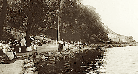 """There's a crowd at Hook Mountain on this afternoon. People are talking, walking, looking at the water. A canoe is pulled up on the small beach. Two dark dots in the water may be swimmers. Beyond the park are buildings of the Manhattan Trap Rock quarrying company."" Photo Credit: Nyack Library via hvrh.org"
