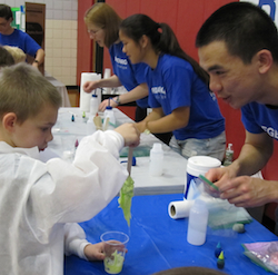 Regeneron's Alexander Wong helps first grader Roman Semon create his very own polymer